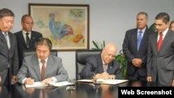 El ministro de Economía cubano Ricardo Cabrisas y el embajador japonés Masaru Watanabe firman el acuerdo.