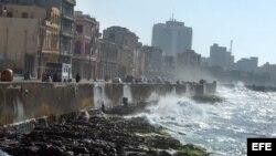 Las olas del mar rompen contra el muro del malecón habanero.