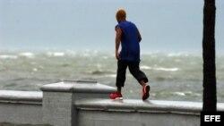 Un joven camina por el muro del malecón de Cienfuegos.