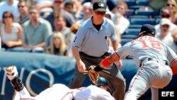 Foto de archivo. El segunda base de los Bravos de Atlanta, Martín Prado (i) es tocado por el primera base de los Nacionales de Washington, Alberto Gonzalez (d) ante la mirada del árbitro Jerry Meals.