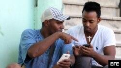 Dos personas navegan por la internet en un dispositivo móvil hoy, viernes 3 de julio del 2015, en una de las zonas habilitadas con Wifi en La Habana (Cuba).