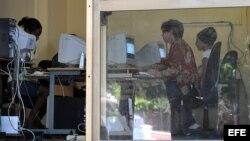 """ARCHIVO. Varias personas consultan Internet en una """"sala de navegación"""", perteneciente a la empresa estatal Correos de Cuba."""