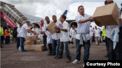 Miembros de la brigada médica cubana enviada a Liberia descargan materiales a su llegada a Monrovia.