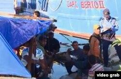 Policías hondureños conversan con algunos de los 16 balseros cubanos que llegaron a La Ceiba desde Manzanillo, Cuba.
