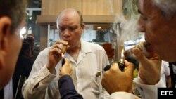 El ministro cubano de Inversión Extranjera, Rodrigo Malmierca (c), enciende un puro durante la inauguración de la feria comercial del XIV Festival del Habano, en La Habana.