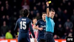 El árbitro Daniele Orsato (d) amonesta con tarjeta amarilla a Stefan Savic (i), del Atlético de Madrid, hoy, miércoles 24 de febrero de 2016.