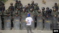Un manifestante protesta frente a integrantes de la Guardia Nacional Bolivariana
