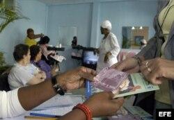 """Una mujer recibe un plegable, un condón y el folleto """"Mujer y SIDA"""" en una peluquería de La Habana."""