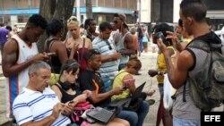 Un hombre (c) ofrece servicios de instalación de aplicaciones y softwares este 26 de septiembre de 2015, en La Habana (Cuba). Desde hace tres meses Cuba vive un inédito, aunque todavía limitado, incremento del acceso a internet con 35 nuevos puntos de con