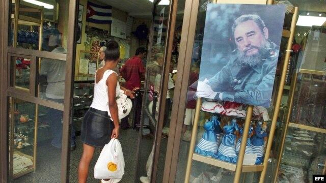Archivo - Una mujer entra en una tienda en La Habana.