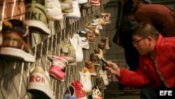 Un joven de Shangai, China, fotografía con su móvil algunas de las zapatillas deportivas.