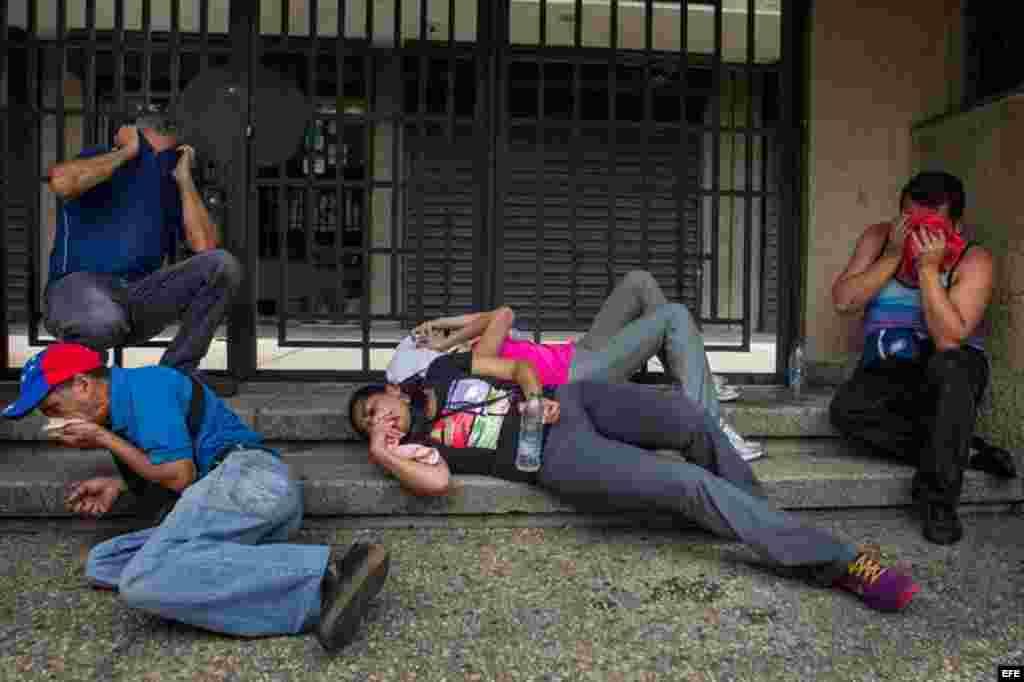Un grupo manifestantes cubre sus rostros luego de recibir gases lacrimógenos lanzados por miembros de la Policía Nacional Bolivariana (PNB) durante una protesta, miércoles 18 de mayo de 2016.