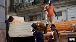 Varios obreros descargan un camión de papas en un mercado de La Habana.