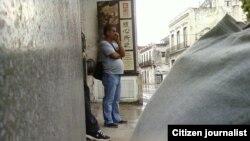 Reporta Cuba. Un agente de la policía vigila a los que realizan protesta. Foto: Arcelio Molina.