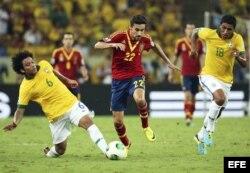 El centrocampista de la selección española Jesús Navas (c) lucha por el balón con los brasileños Marcelo Vieira (i) y Paulinho (d) durante la final de la Copa Confederaciones.