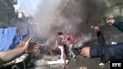 Varios iraquíes sujetan mangueras para tratar de apagar el fuego causado por un coche bomba en un distrito de Bagdad, Irak hoy, lunes 27 de mayo de 2013.
