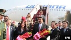 Fotografía cedida por Prensa de Miraflores del presidente de Venezuela, Nicolás Maduro (c-d), acompañado de su esposa, Cilia Flores (c-i), a su llegada a Pekín (China).