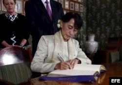 La opositora birmana Aung San Suu Kyi firma en el libro de honor en la sede del Instituto Nobel en Oslo, Noruega, el sábado 16 de junio de 2012