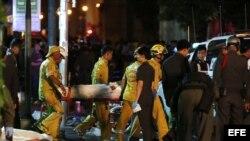 Miembros de los servicios de emergencias traslandan un cadáver en el lugar donde ha explosionado una bomba junto a un templo budista en Bangkok, Tailandia, hoy, 17 de agosto de 2015.