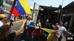 Manifestantes gritan consignas a un grupo de policías en San Cristobal (Archivo)