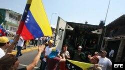 Manifestantes gritan consignas a un grupo de policías durante una marcha contra el gobierno de Nicolás Maduro en San Cristobal, Venezuela