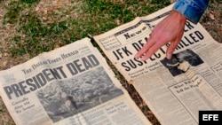 Un hombre muestra un periódico de 1963 que informa sobre el asesinato de Kennedy en el monumento en memoria de John F. Kennedy en Dealey Plaza, Dallas, Texas, EEUU.