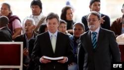 """El presidente de Colombia, Juan Manuel Santos (i), recibe el informe """"¡Basta ya! Colombia: memorias de guerra y dignidad"""", de manos del director del Centro Nacional de Memoria Histórica, Gonzalo Sánchez."""