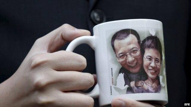 Un activista pro democrático muestra un retrato del disidente chino Liu Xiaobo y de su esposa Liu Xia.