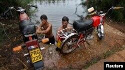 Un grupo de jóvenes lavan sus motocicleetas en el Río Guanímar.