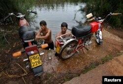 Un grupo de jóvenes lavan sus motocicletas en el Río Guanímar.