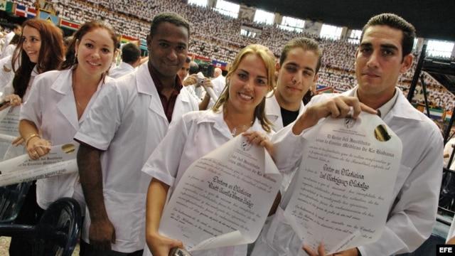 Médicos cubanos graduados muestran sus diplomas durante el acto oficial de creación de un contingente médico internacional.