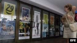 Una mujer observa varios carteles de las películas que exhibe un cine en La Habana (Cuba).