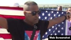 Daniel Llorente sostiene la bandera estadounidense mientras espera la llegada del crucero Adonia.