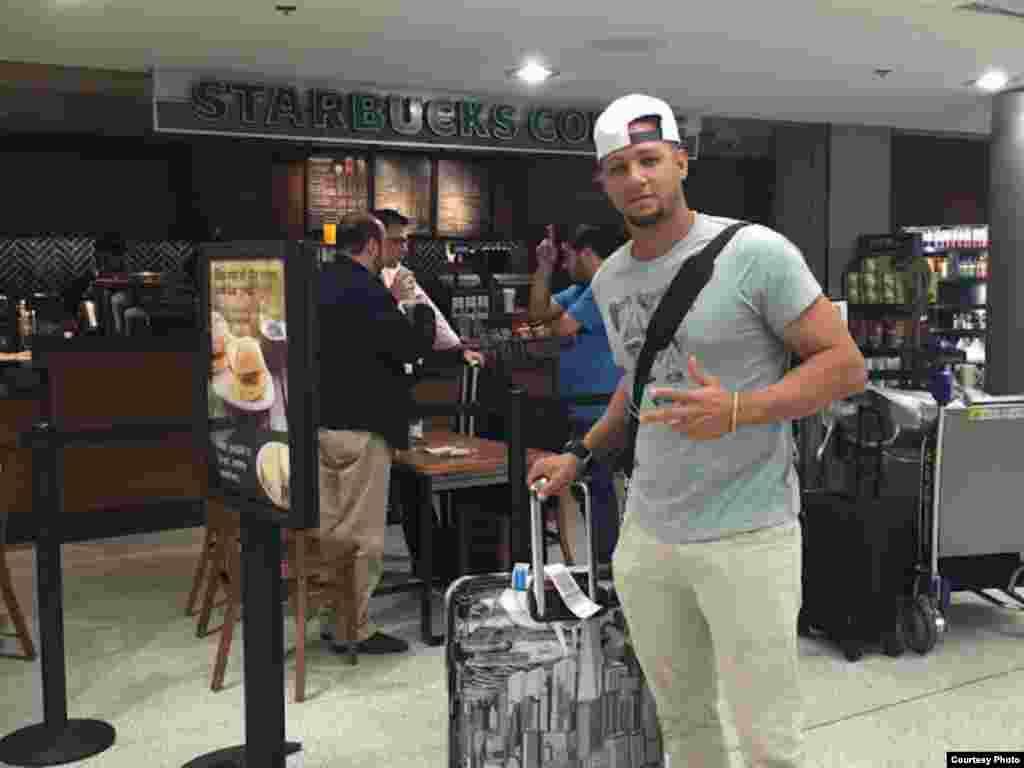 Yulieski Gourriel pasa con su equipaje ante una cafetería Starbucks en el Aeropuerto Internacional de Miami (SwingCompleto)