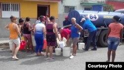 Vecinos de Santiago de las Vegas, en Boyeros hacen cola frente a una pipa de agua.