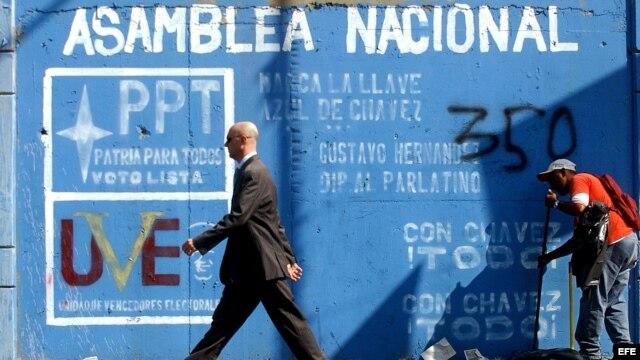 Un hombre pasa frente a un mural invitando a votar en las elecciones para elegir los diputados de la Asamblea Nacional. Foto de archivo.