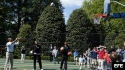 """Barack Obama tira a canasta durante un partido de baloncesto con los miembros del equipo Harlem Globtrotters durante el llamado """"Easter Egg Roll""""."""