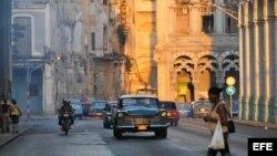 Varios autos circulan por una calle de La Habana Vieja.