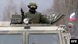 """Un militar uniformado armado, fotografiado a bordo de un vehículo de infantería ruso """"GAZ Tigr"""" en el exterior de un cuartel de una unidad del ejércitio ucraniano en la localidad de Perevalnoye, a las afueras de Simferopol, en la península de Crimea."""