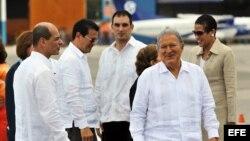 Salvador Sánchez Cerén (d) y su esposa, Margarita Villalta, son recibidos por el vicecanciller cubano Rogelio Sierra (i) a su llegada a La Habana.