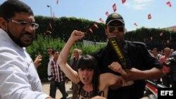 Un agente de seguridad detiene a una de las tres activistas arrestadas frente al Ministerio de Justicia en Túnez (Túnez).