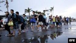 Varios supervivientes esperan en fila listos para abandonar la ciudad en Tacloban (Filipinas) el martes 12 de noviembre de 2013.