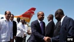 El primer ministro de Haití, Laurent Salvador Lamothe (c), saluda a varios oficiales cubanos acompañado por el vicecanciller de Cuba, Rogelio Sierra (i)