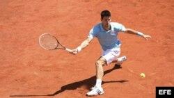 El tenista serbio Novak Djokovic golpea la bola contra el letón Ernests Gulbis.