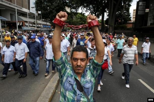 """Un hombre simboliza con cadenas la prisión que es el sistema socialista hoy, jueves 1 de septiembre de 2016, en una manifestación denominada """"Toma de Caracas""""."""
