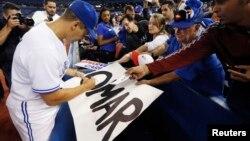 Omar Vizquel firma autógrafos tras finalizar el partido con los Mellizos de Minnesota en octubre de 2012.