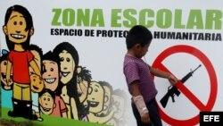 Una señal que prohibe el uso de armas en una pared de una escuela en el casco urbano de Toribio, Cauca, en Colombia.