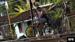 Un padre y su hijo montan en bicicleta por las vías del tren en el poblado de Guayacanes, en la provincia de Ciego de Ávila (Cuba). EFE/Alejandro Ernesto