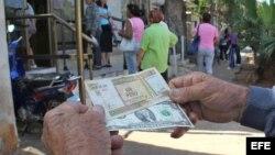 Un hombre muestra un peso convertible cubano y un dólar estadounidense frente a una oficina de Western Union en La Habana (Cuba).