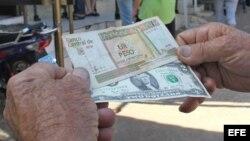Un hombre muestra un peso convertible cubano y un dólar estadounidense frente a una oficina de la Western Union en La Habana (Cuba).